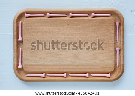 Empty cutting board with different wooden golf tees - stock photo