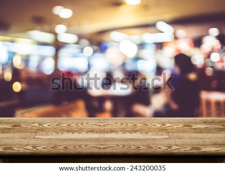 Empty dark wood table top with coffee shop blur with bokeh background,Product display template. - stock photo