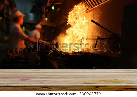 Empty dark wood table with fire gas burn is cooking on iron pan