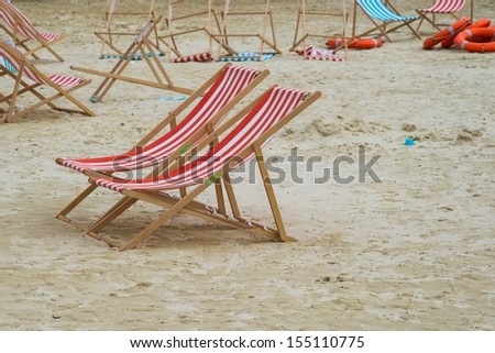 Empty deck chairs on the sand beach. Wet sand, blue mold, nobody around, bad weather. - stock photo
