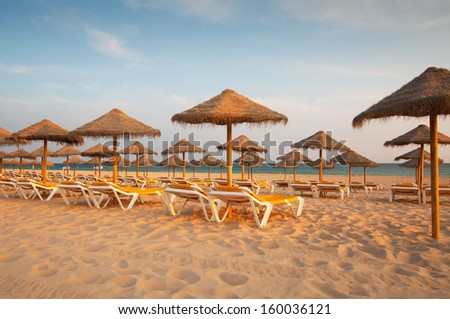 Empty deck loungers in the beach at sunset. Paradise in Algarve, Portugal - stock photo