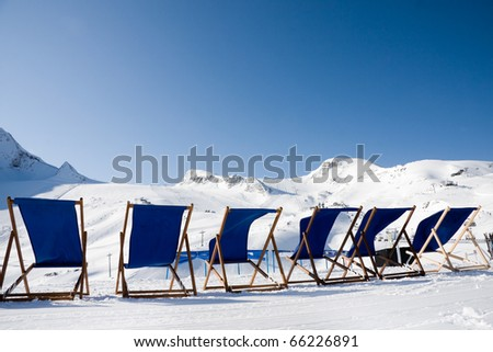 Empty deckchairs in front of ski slopes in alps mountains - stock photo