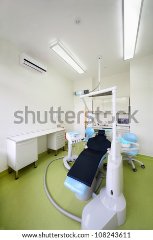 Empty dental clinic. Chair for patient and large drill for dentist.