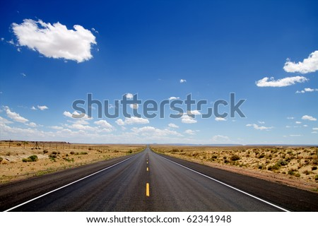 Empty desert road stretching to horizon - stock photo
