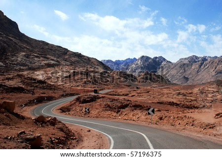 Empty desert road with mountain and blue sky - stock photo