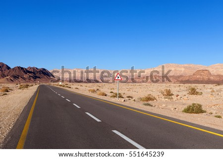 Empty desert road with mountains and blue sky in the background