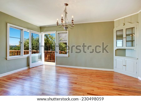 Empty dining room interior with hardwood floor, light mint walls, built-in cabinet and walkout deck - stock photo