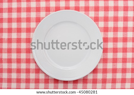 Empty dinner plate on red and white checked gingham tablecloth