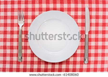 Empty dinner plate with fork and knife on red and white checked gingham tablecloth - stock photo