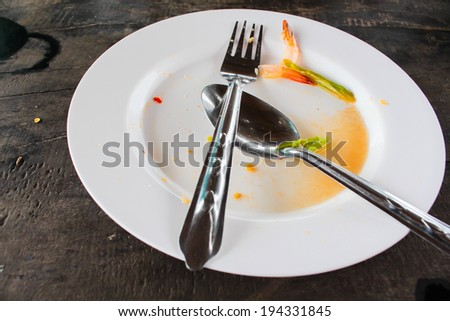 empty dirty plate seafood paste on wooden table left after lunch, samui thailand - stock photo