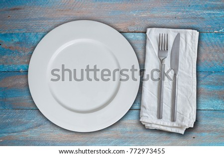 Empty dish and cutlery on blue shabby chic wood.