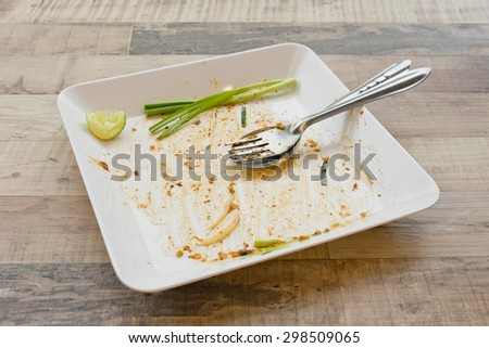 Empty dish but still has spring onion after food on the table - stock photo
