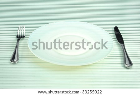 Empty dish, fork and knife - stock photo