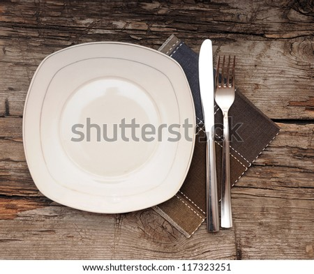 Empty dish, knife and fork and brown napkin on old wood table - stock photo