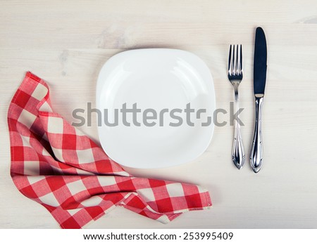 Empty dish, knife and fork and red napkin on wood table - stock photo