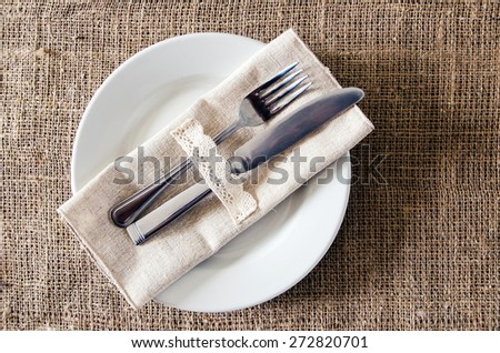 Empty dish, knife and fork on a napkin of burlap - stock photo