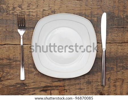 Empty dish knife and fork on grungy wood table - stock photo
