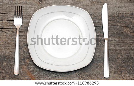Empty dish knife and fork on wood table - stock photo