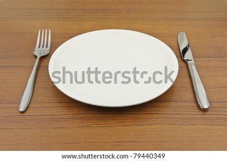 Empty dish, knife and fork on wood table - stock photo
