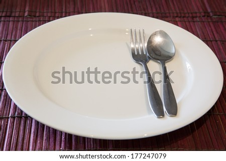 empty dish with spoon and fork - stock photo
