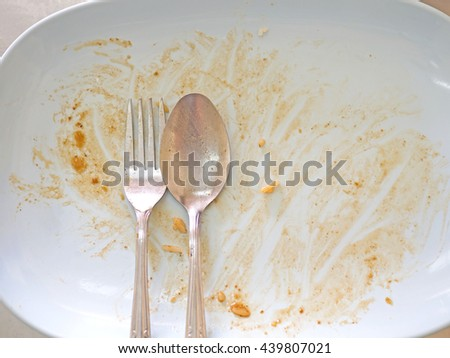 Empty dish with spoon and fork after food on the table - stock photo