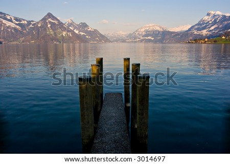 Empty dock in calm lake with mountains in the horizon. Buochs, Switzerland. - stock photo
