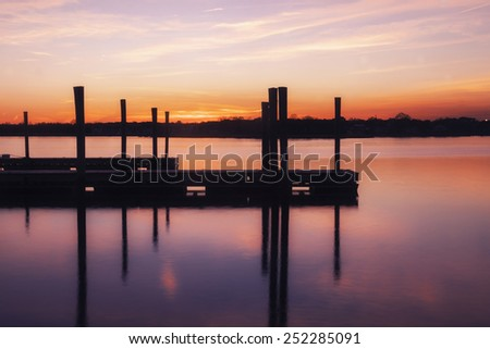 Empty Dock On Water Under a Pink and Orange Sunset