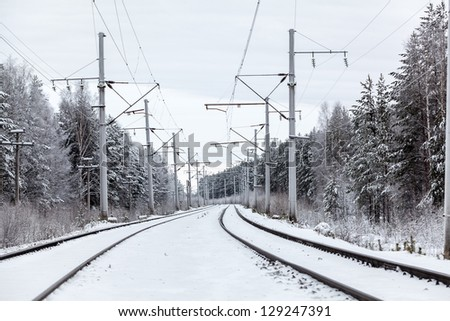 Empty electric mainline railroad in winter forest - stock photo