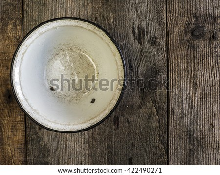 Empty enameled metal bowl on old weathered wooden surface - stock photo