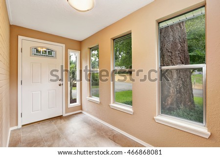 Empty entryway with tile floor, beige walls and white front Northwest, USA.