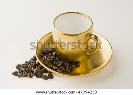 Empty Espresso gold coffee cup with beans on white - stock photo