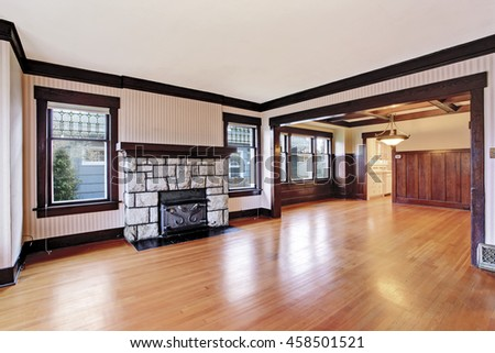 Empty Family room with white ceiling and dark brown trim, antique stone fireplace and hardwood floor. View of unfurnished room with wood paneled walls. Northwest, USA - stock photo