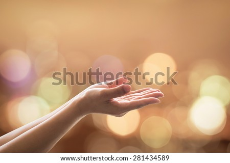 Empty female open human hands prayer with palms up and candle lights bokeh in natural warm gold color tone: Pray for support and help concept: Night of power, destiny: Humanitarian aid campaign    - stock photo