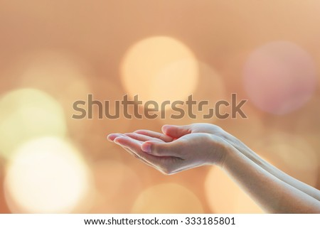 Empty female open human hands prayer with palms up and candle lights bokeh in natural warm gold color tone: Pray for kindness, support, help, power and destiny concept: Humanitarian aid campaign/ idea - stock photo