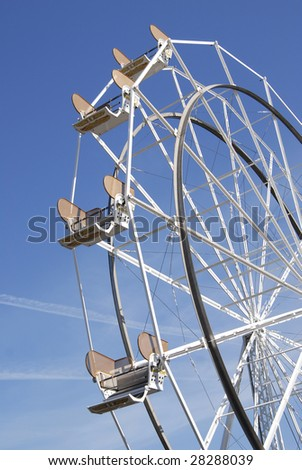 Empty Ferris Wheel on a bright sunny day with blue sky. - stock photo