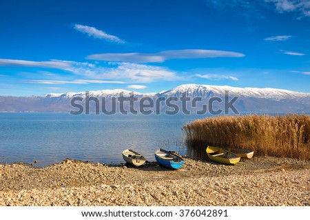 Empty fishing boats sitting on the lake coast with mountains in the background