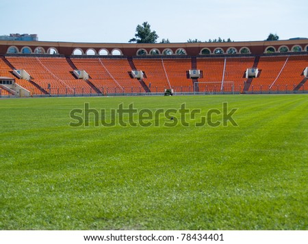 empty football field with green grass playground and orange seats  - stock photo