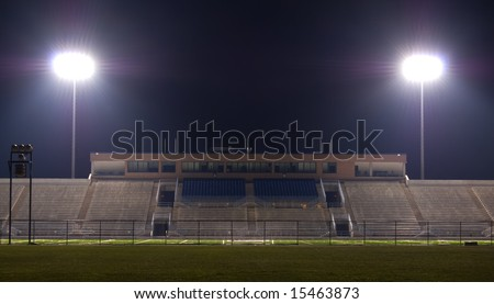 Empty football stadium at night with the lights on