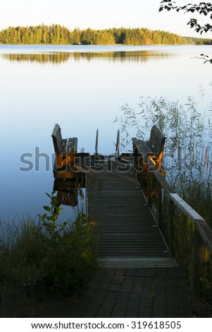 Empty footbridge with a bench on a lake at sunrise - stock photo