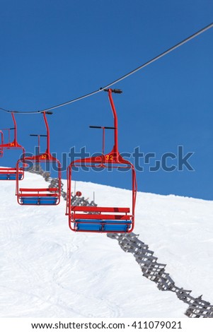 empty four chairs of ski lift going down from the peak of the mountain