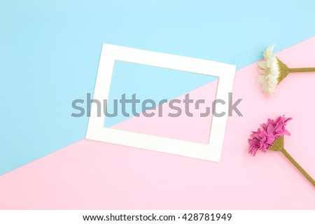 Empty frame and flowers flat lay on blue and pink pastel background with copy space. Soft effect filter. - stock photo