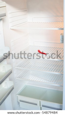 Empty fridge with only chili pepper on the shelf - stock photo
