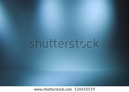 Empty gallery wall with lights for images and advertisement. Blue background - stock photo