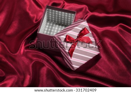 Empty gift box with red ribbon on red satin background - stock photo