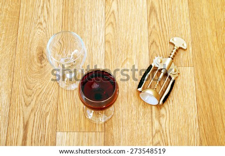 empty glass and a glass of wine and a corkscrew on a wooden table - stock photo