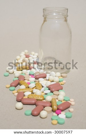 Empty glass bottle and pile of spilled pills