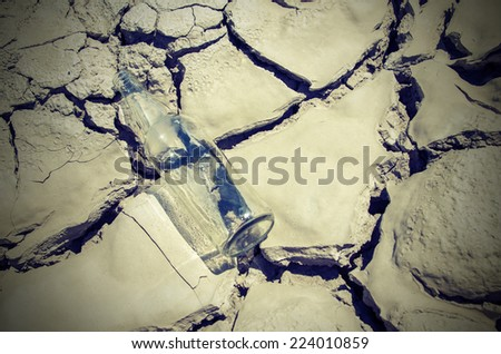 Empty glass bottle for water lies on the dry desert land - stock photo