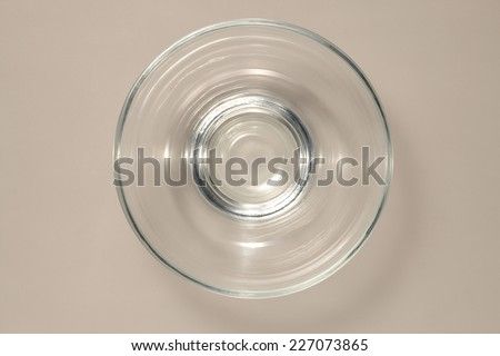Empty Glass Bowl isolated on Grey Background with Real Shadow. Top View with Copy Space for Text or Image - stock photo