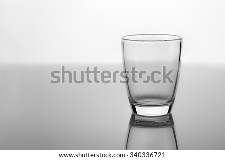 Empty glass for water, juice or milk on white background grey glossy  floor