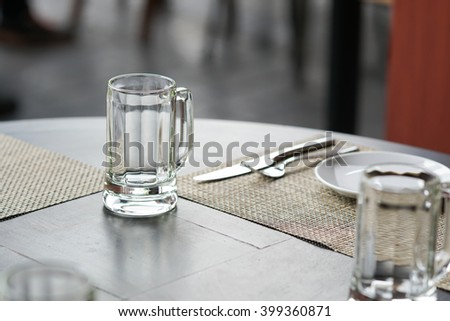 empty glass mug, cutlery and white dish on wooden table